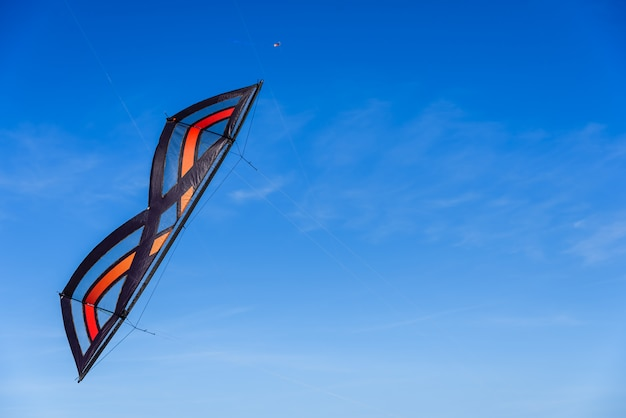 Acrobatic stunt kite flying in the blue sky.