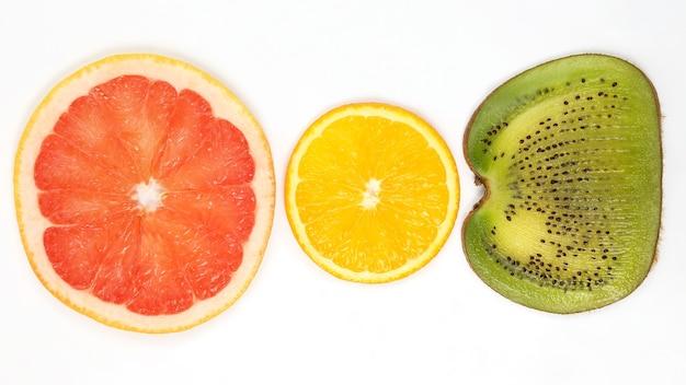 흰색 배경에 얇게 썬 키위, 오렌지, 자몽을 가로질러. 과일의 유용한 비타민 식품