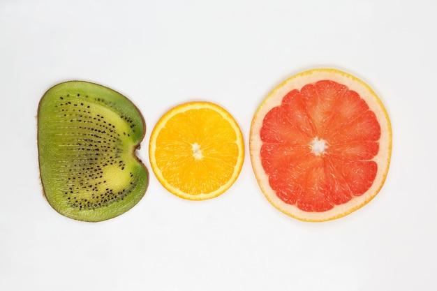 Через нарезанный киви, апельсин и грейпфрут на белом