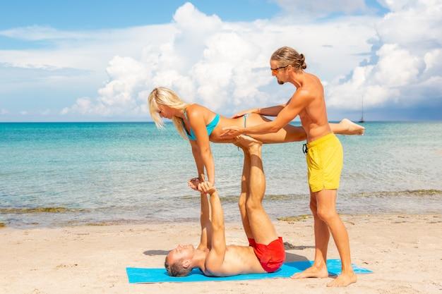 Два молодых мужчины и женщины на пляже, занимаясь йогой фитнес упражнения вместе. элемент acroyoga для силы и баланса