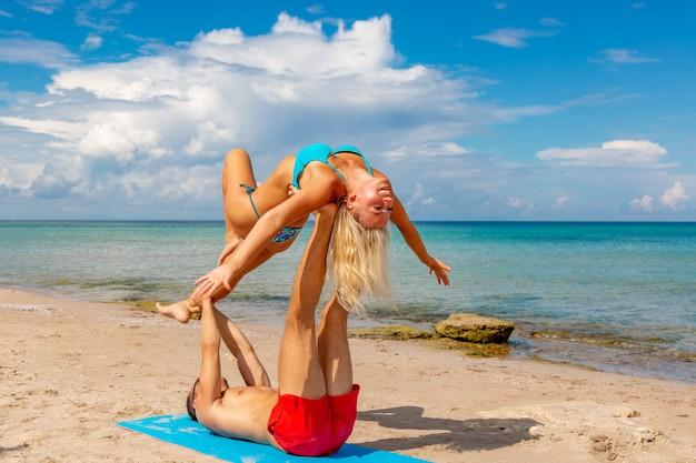 Молодые пары женщина и люди на пляже делая йогу фитнеса работают совместно. элемент acroyoga для силы и баланса