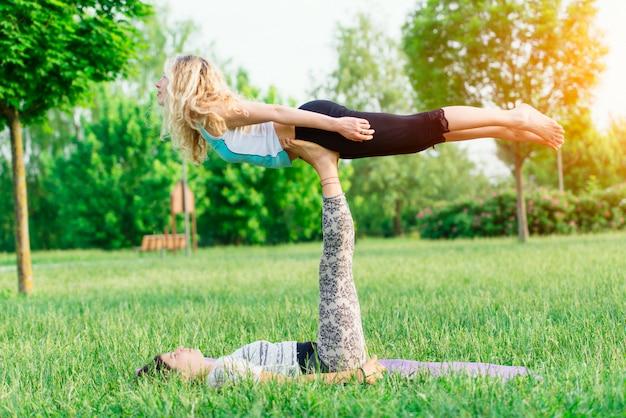 公園でacroyogaを練習するカップル