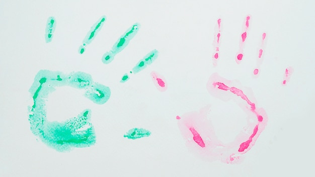 Acrylic green and pink watercolor handprint on white surface