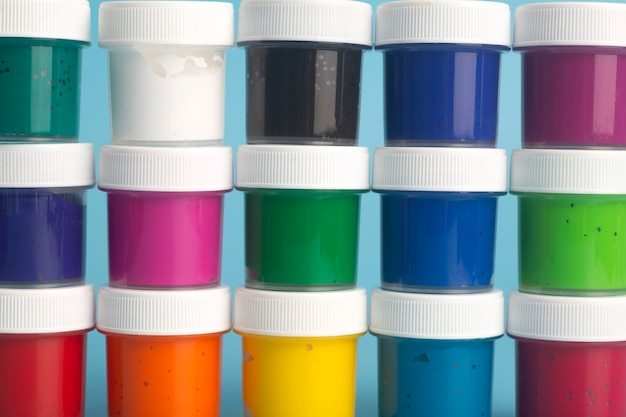 青い背景にさまざまな色のアクリル絵の具。塗装用塗料。