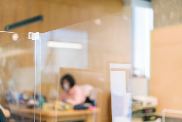 マスクを身に着けているぼかし従業員とオフィスの机の上のアクリルプレキシガラスセパレーターの設定。