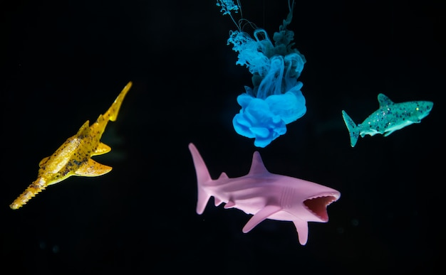 Acryllic color dissolving in water with toy sharks
