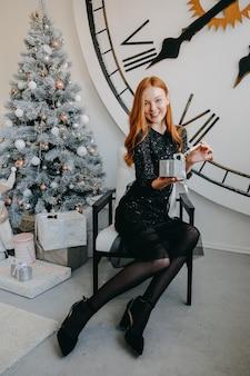 Акт рождественских подарков, дающий красивую рыжую молодую женщину, держащую рождественские подарки, счастливая молодая женщина