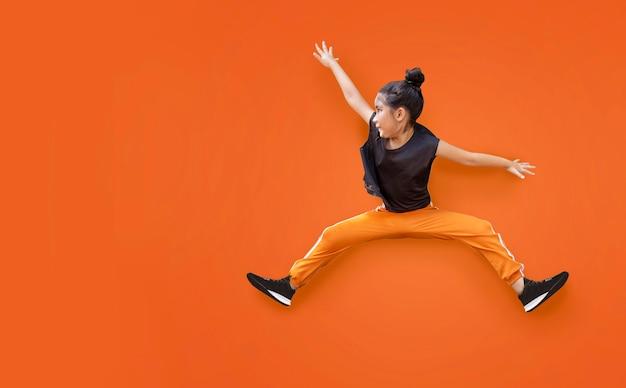 Азиатская девочка-девочка, прыгающая в высоту, на изометрическом фоне в спортивной одежде для упражнений (включая путь)