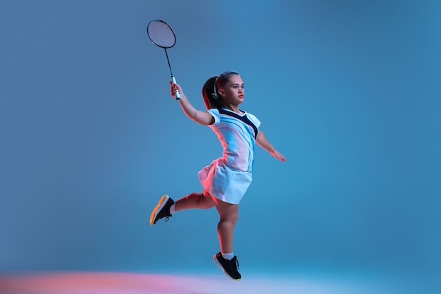 동작. 네온 불빛에 파란색으로 격리된 배드민턴에서 연습하는 아름다운 난쟁이 여자