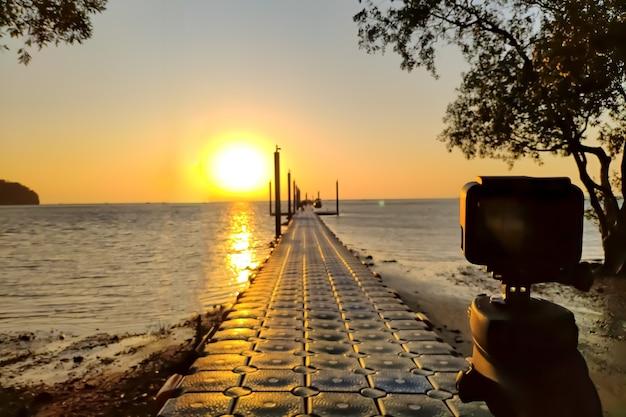 三脚に取り付けられたアクションカメラで、桟橋と黄金の日の出のタイムラプスを作成します