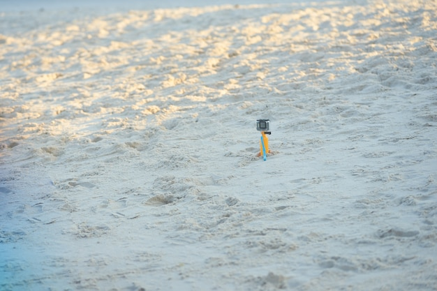 Action camera in plastic transparent housing on stand on sand beach