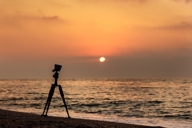 Action camera on a tripod on a sandy beach shooting a video of sunset over the sea.