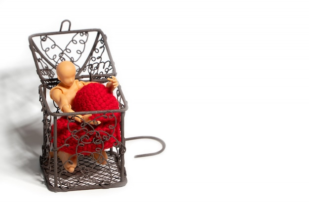 Action figure sitting in cage and holding red heart on white background