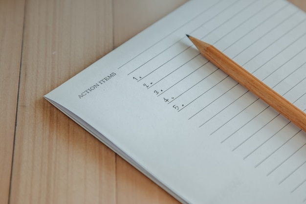 Action items list write in notebook and pencil