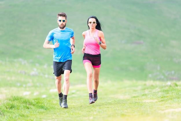夏の丘陵地帯でのランナーの行動。男性と女性