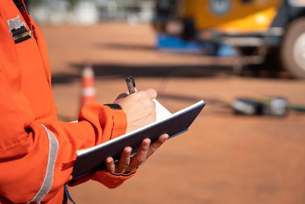 크레인 트럭 차량의 배경이 흐린 체크리스트에 안전 담당자의 조치가 기록되고 있습니다. 무거운 작업 개념 사진의 안전 검사 감사, 사람의 손에 선택적 초점.