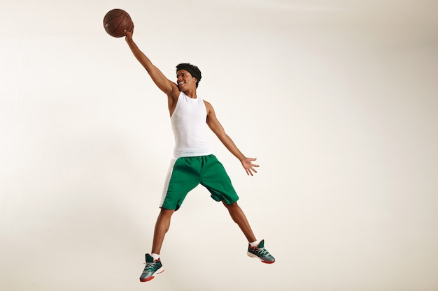 Action photo of a happy young black athlete wearing white shirt and green shorts jumping high to grab a vintage basketball on white
