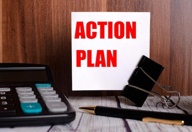 アクションプランは、電卓とペンの横にある木製の背景の白いカードに書かれています