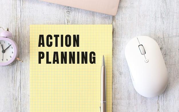 노트북 옆에 나무 작업 테이블에 누워 노트북에 쓰여진 행동 계획 텍스트. 비즈니스 개념.