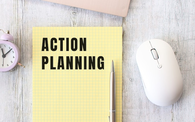 Action planning text written in a notebook lying on a wooden work table next to a laptop. business concept.
