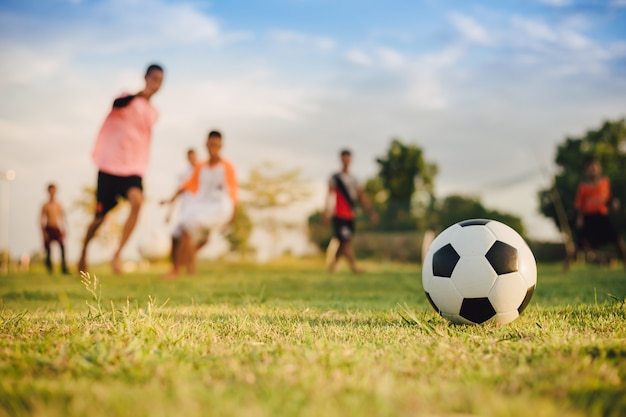 Action sport outdoors of a group of kids having fun playing soccer