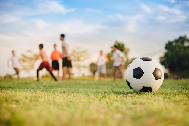Action sport outdoors of kids having fun playing soccer football