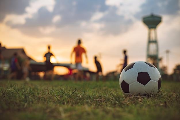 運動のためにサッカーサッカーをしている子供たちの屋外でのアクションスポーツ