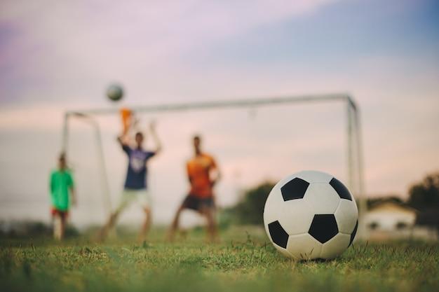 運動のためにサッカーサッカーをする子供たちの多様性の屋外アクションスポーツ