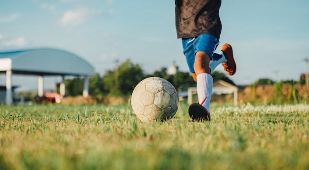An action sport picture of kids playing soccer football for exercise at the green grass field