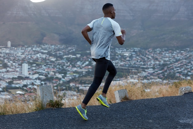 Action view of male jogger covers long distance, dressed in casual leggings and t shirt, poses over mountains view on road, has sportshoes, catches breath during cardio workout. motion, speed concept