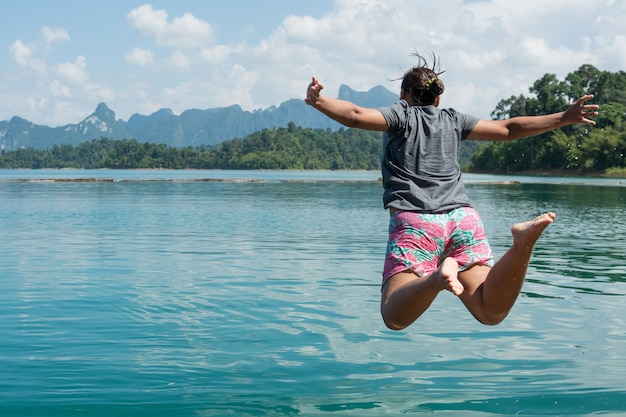Action of young woman jumping into a lake.