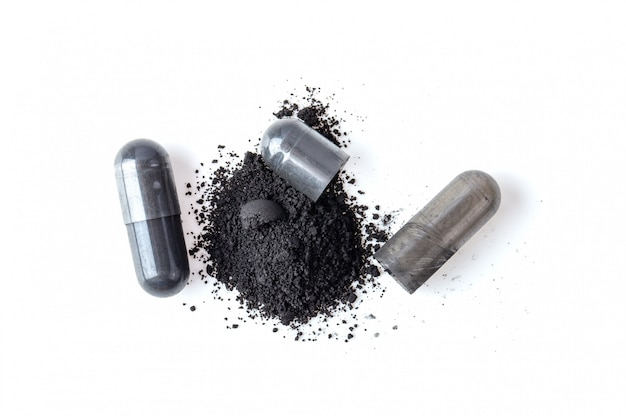 Капсула и порошок активированного угля изолированные на белизне. вид сверху