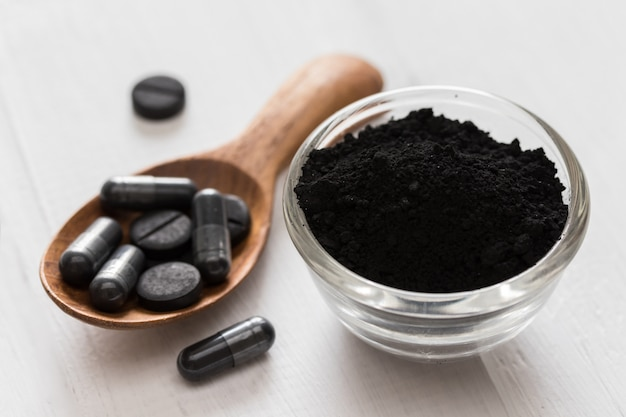 Activated charcoal powder in a glass bowl and pills on a spoon on white wooden background
