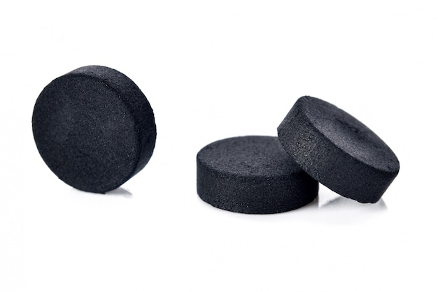 Activated charcoal tablet pills isolated on white background