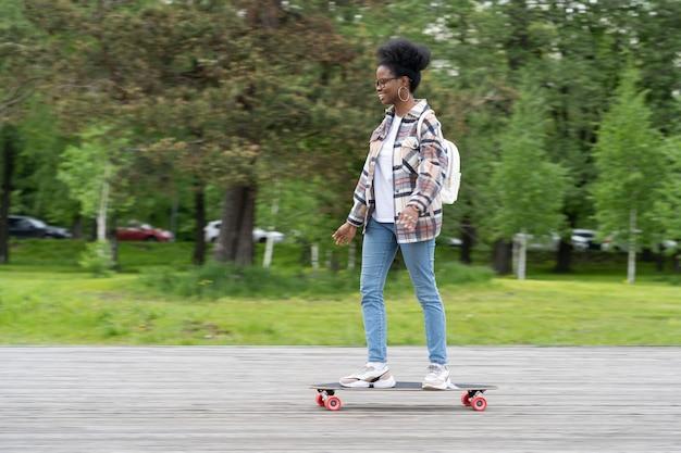 활동적인 아프리카계 미국인 여성은 도시 공원에서 스케이트보드를 타고 트렌디한 캐주얼 여성 스케이트보드를 탄다