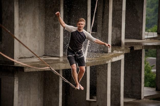 Активный и смелый молодой человек балансирует на слеклайне