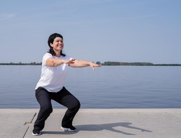 강변 근처에 쪼그리고 앉는 적극적이고 행복 한 고위 여자