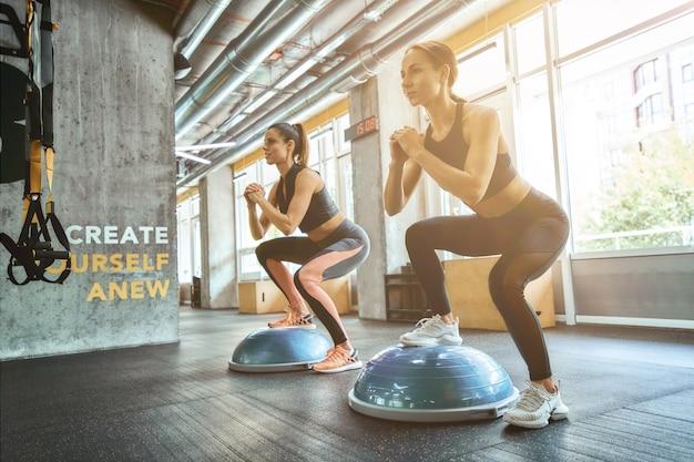 Активный и здоровый образ жизни в полный рост двух молодых спортсменок в спортивной одежде, делающих приседания