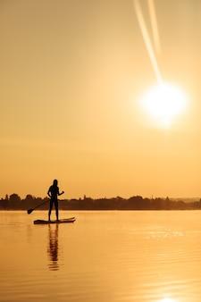 霧の湖でスタンドアップパドルで長いパドルで歩き回っているアクティブで健康な男性。