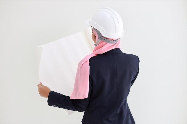 スタジオで自信を持って持株の青写真を笑顔青いスーツのアクティブでスマートなイスラム教徒エンジニア若いアジア女性。ヒジュブと美しい少女と孤立した白い背景の肖像画。広告のコンセプト。