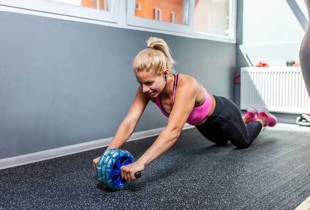 피트니스 수업에서 ab 롤러 복부 운동을 하는 활동적이고 강한 피트니스 여성. 슬리밍 개념, 건강한 라이프 스타일