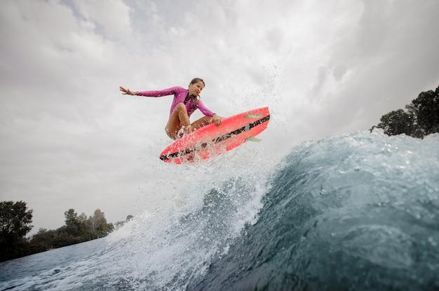적극적이 고 젊은 여자 서퍼 하늘을 파란색 튀는 파도 위로 점프