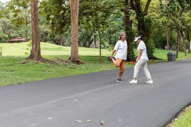 公園でジョギングスポーツウェアでアクティブなアジアカップルシニア。