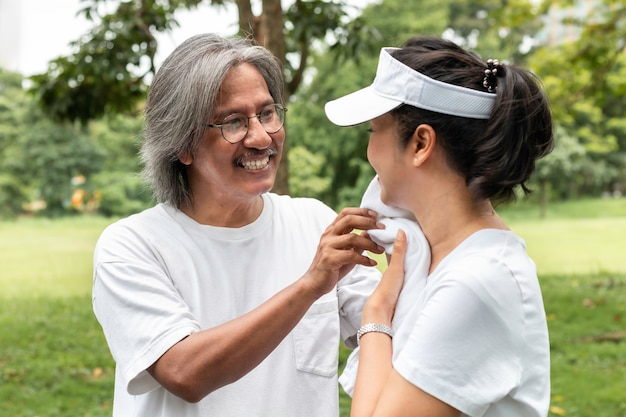 Active asian couple senior in sportswear are wiping sweat after exercising in the park.