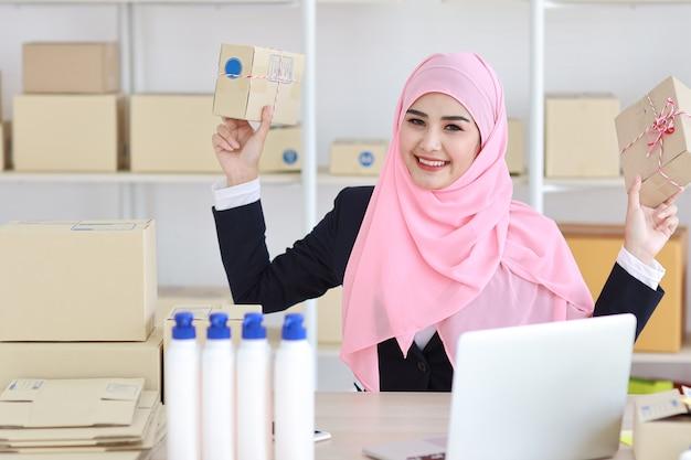 Активная азиатская мусульманская женщина в синем костюме сидит и работает с компьютером и показывает доставку онлайн-упаковки
