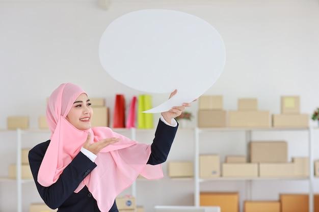 オンラインパッケージボックス配信で白い吹き出しを立って保持している青いスーツのアクティブなアジアのイスラム教徒の女性