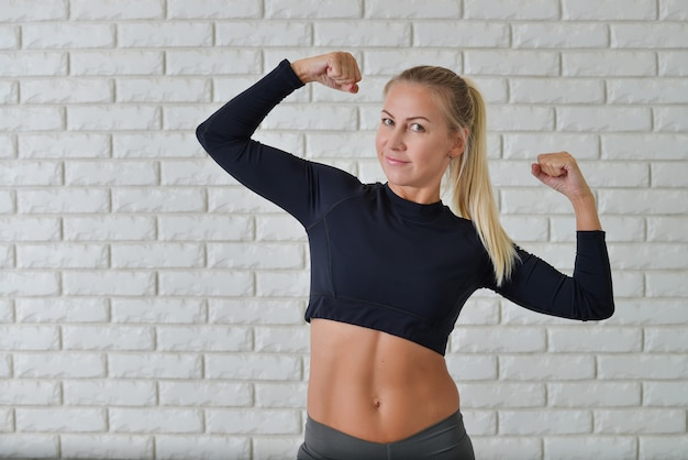 Active athletic sporty woman in sport outfit standing showing biceps muscles against white brick wall