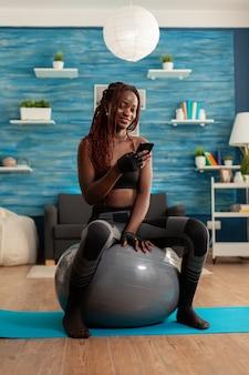 Активная спортивная женщина болтает на смартфоне, сидя на швейцарском мяче в домашней гостиной, после тренировки на коврике для йоги, чтобы стать сильнее и вести здоровый образ жизни