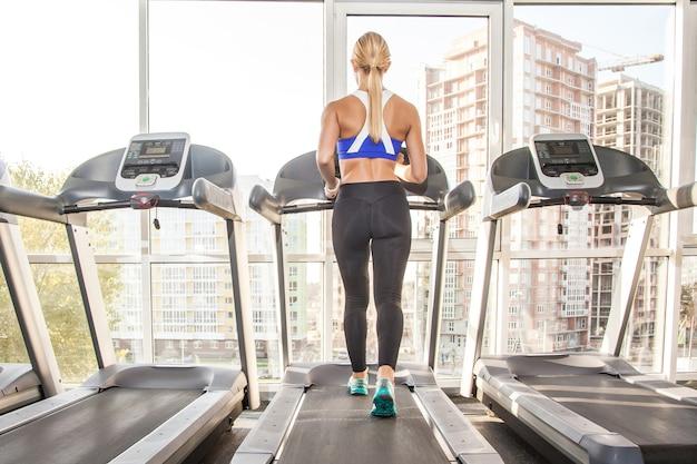 朝の競馬場でジョギングしている完璧なボディのアクティブなアスレチック女性。スタジオショット