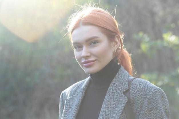Активная красивая рыжая собравшая волосы девушка гуляет по лесу